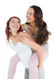 Happy young female piggybacking cheerful friend Royalty Free Stock Image