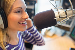 Happy young female radio host broadcasting in studio Royalty Free Stock Photos