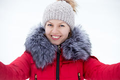 Happy young female in red winter jacket taking self-portrait, ou Royalty Free Stock Images