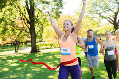 Happy young female runner winning on race finish. Fitness, sport, victory, success and healthy lifestyle concept - happy women winning race and coming first to Royalty Free Stock Images