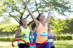 Happy young female runner winning on race finish Stock Photos