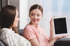 Free Happy Young Female Showing Digital Tablet To Female Friend Sitting On Sofa Royalty Free Stock Photo - 127749955