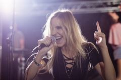 Happy young female singer performing at nightclub Royalty Free Stock Photo