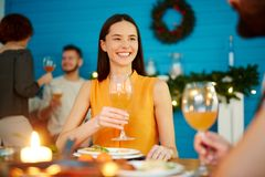 Smiling woman holding glass at dinner with friends stock image