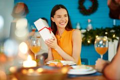 Smiling woman holding present at dinner with friends royalty free stock photo