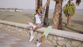 Happy young female skateboarder sitting cheering stock video footage