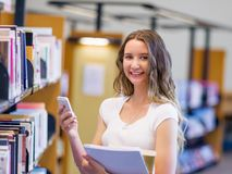 Happy female student holding books at the library Stock Images