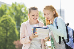 Happy young female students reading book at college campus Royalty Free Stock Photography
