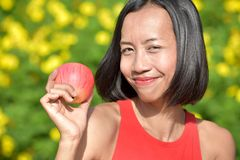 Happy Young Filipina Person With An Apple. An attractive young asian person stock photos