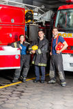 Happy Young Firefighters Standing Against Trucks Stock Image