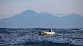 A small boat at the pier of ocean with mountains in the background. A small boat bobs on the waves in the early morning at the pier of ocean with mountains in stock video footage