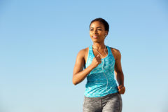 Happy young fitness woman running with earphones Royalty Free Stock Images