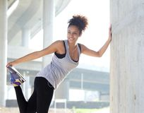 Happy young fitness woman stretching outdoors Stock Images