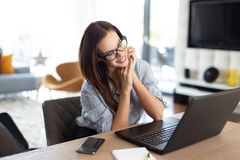 Happy young freelancer woman smile at laptop stock image