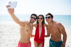Happy young frends taking selfie through mobile phone at beach Royalty Free Stock Photos