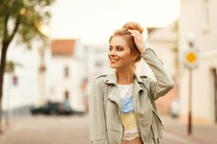 Happy young fresh woman with a smile in a fashionable jacket. And lace t-shirt walking in the city stock photography