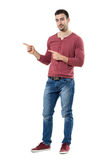 Happy young friendly man presenter pointing finger showing copyspace looking at camera Stock Image