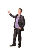Happy young friendly smiling businessman pointing finger Royalty Free Stock Image