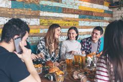 Happy young friends celebrating with pizza burgers and drinking beer at bar restaurant. Friendship concept with young people enjoying time together and having stock photos
