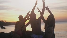 Happy young friends with children having fun singing song and dancing rising their hands on a tropical beach during. Happy young friends with children having fun stock video footage
