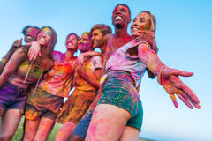 Happy young friends with colorful paint on clothes standing together at holi festival. Low angle view of happy young friends with colorful paint on clothes Stock Photography