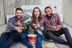 Happy young friends drinking beer and eating pizza at home Royalty Free Stock Photos