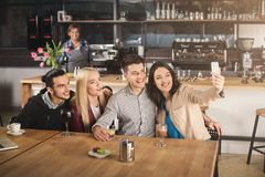 Happy young friends drinking coffee at cafe. Happy young company of friends drinking coffee, talking and taking selfie while sitting at modern coffee shop, copy Royalty Free Stock Images