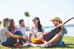 Happy young friends having picnic in the park.They are all happy,having fun,smiling and playing guitar.  Stock Image