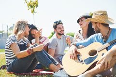 Happy young friends having picnic in the park.They are all happy,having fun,smiling and playing guitar.  Royalty Free Stock Photos