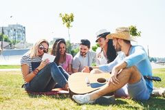 Happy young friends having picnic in the park.They are all happy,having fun,smiling and playing guitar.  Stock Photos