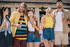 happy young friends holding beer bottles while spending time together royalty free stock images