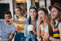 happy young friends holding beverages and looking away while spending time together stock images