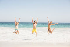 Happy young friends jumping on the beach. With arms outstretch Royalty Free Stock Photography