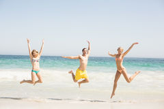 Happy young friends jumping on the beach. With arms outstretch Stock Photo