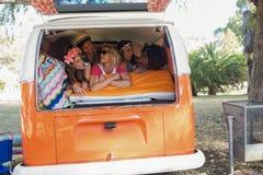 Happy young friends lying in camper van Stock Image