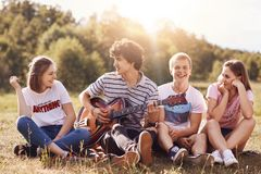 Happy young friends sing songs to guitar, have joy together, recreat outdoor, sit on green grass. Curly handsome male teenager pla. Ys guitar, enteratins his stock photo