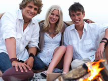 Happy young friends sitting by bonfire at beach in Stock Images