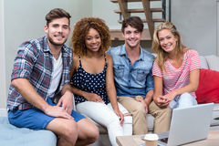 Happy young friends sitting on sofa at home Royalty Free Stock Photo