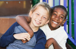 Happy young friends sitting together. Happy African and Caucasian male child friends on playground set Stock Photo
