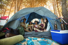 Happy young friends sitting together in tent Royalty Free Stock Images