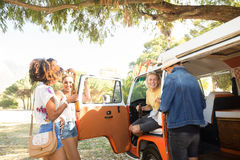 Happy young friends standing by camper van at campsite Stock Images