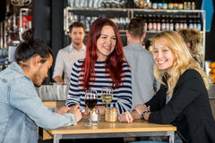 Happy Young Friends At Table In Restaurant royalty free stock photography