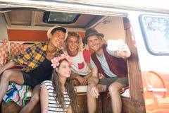Happy young friends taking selfie in camper van Stock Image