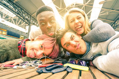 Happy young friends taking selfie indoors with back lighting royalty free stock photo
