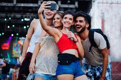 Happy friends taking selfie at music festival. Happy young friends taking selfie at music festival Royalty Free Stock Images