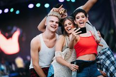 Happy friends taking selfie at music festival Stock Photo