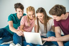 Young friends using laptop Stock Photo
