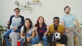Happy young friends watching sports game on TV and celebrating favourite team victory at home. Indoors stock footage