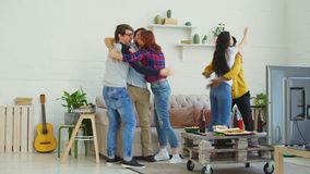 Happy young friends watching sports game on TV jumping and celebrating victory of favourite team at home. Indoors stock footage
