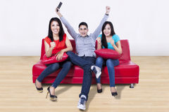 Happy young friends watching tv at home Royalty Free Stock Photo